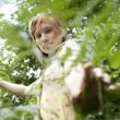Teenage girl peering through forest foliage, looking into the camera. — Stock Photo