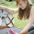 Teenage girl with a picnic basket in the forest. - Stock Photo