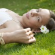 Side view of teenage girl laying down on grass. — Stockfoto