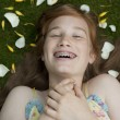 Stock Photo: Overhead view of teenage girl with flower petals, laughing and wearing braces.