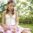 Teenage girl pulling petals off a daisy flower. - Foto Stock
