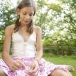 Teenage girl pulling petals off a daisy flower. - Stock Photo