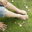 Overhead view of young girl's legs and feet, with flowers between the toes. — Stock Photo