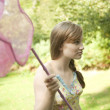 Teenage girl holding a butterfly net in the forest. — Stock Photo