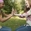 Teenage girls touching hands in forest. - Stock Photo