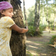 Stock Photo: Teenage girls hugging trees in forest.