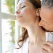 Mature man kissing woman's neck by large french window. — Stock Photo