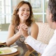 Mature couple enjoying lunch in a hotel terrace, holding hands. — Stock Photo