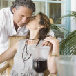 Mature woman kissing man while having a red wine drink at home. — Stok fotoğraf