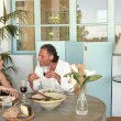 Mature couple eating and drinking together at garden table, while having a lively conversation. — Stock Photo