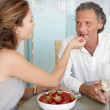 Stock Photo: Woman feeding man strawberries while sitting on an outdoors table at home.