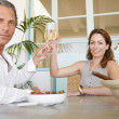 Mature cople toasting with champagne and eating strawberries, smiling. — Stock Photo