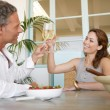 Mature cople toasting with champagne and eating strawberries. — Stock Photo