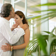 Close up of a mature couple kissing at home, standing by large glass doors. — Stock Photo