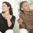 Mature couple sharing earphones while listening to music with an mp4 in their home's living room. — Stock Photo
