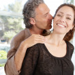 Close up portrait of a mature couple being playful and kissing at home — Stock Photo