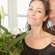 Mature couple with bunch of flowers at home. — Stock Photo #20083823