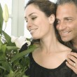 Mature man giving a woman a bunch of flowers at home. — Stock Photo