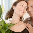 Close up of a mature couple with bunch of flowers at home. — Stock Photo