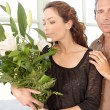 Mature couple with bunch of flowers at home. — Stock Photo