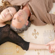 Over head view of a mature couple laying down on carpet at home. — Stock Photo #20083837