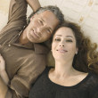Over head portrait of a mature man and woman laying down on carpet, holding hands and smiling at camera. — Stock Photo