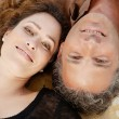 Over head view of a mature couple laying down on carpet at home, smiling. — Photo