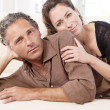 Mature couple lounging on white sofa at home. — Stock Photo