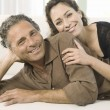 Mature couple laying down on a white sofa, smiling at the camera. — Stock Photo