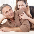 Stock Photo: Mature couple lounging on white sofa at home.