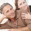 Foto Stock: Mature couple lounging on white sofat home.