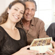 Mature couple with box of chocolates at home. — Stock Photo