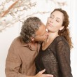 Foto Stock: Mature couple kissing while lounging at home.
