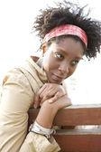 Unga attraktiva afroamerikanska kvinna är omtänksamma medan du sitter på en bänk i en park. — Stockfoto