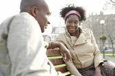 Jonge afrikaanse amerikaanse echtpaar zittend op een bankje in een park in de city of london. — Stockfoto