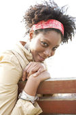 Young attractive african american woman smiling while sitting on a bench in a city park. — Stock Photo