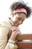 Jeune femme afro-américaine attrayante, souriant tout en étant assis sur un banc dans un parc de la ville. — Photo
