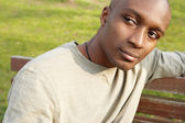 有魅力的非洲裔美国人正坐在公园的长凳上周到. — 图库照片