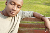 Attractive african american man being thoughtful while sitting on a bench in a park. — Stock Photo