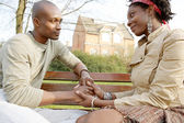 Fashionabla par hålla händer medan du sitter på en träbänk i en park i staden. — Stockfoto