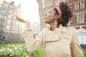 Beautiful young black woman holding the sun in her hand at sunset while visiting London city. — Stock Photo