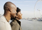 African american couple on Westminster Bridge looking at London's skyline — Stock Photo