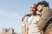 Attractive black tourist couple standing by Big Ben while visiting London city on vacation — Stock Photo