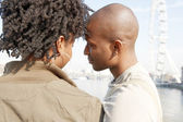 Attractive black couple standing by the river Thames — Stock Photo