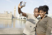 Tourist couple taking a picture of themselves while visiting Big Ben in London city. — Stock Photo