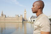 Profile view of a young tourist walking by Big Ben whilst visiting London city. — Stock Photo