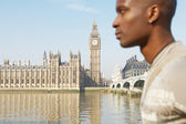 Wide view of Westminster Palace and the river Thames with a tourist walking past out of focus. — Stock Photo