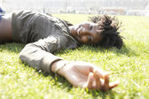 Young african american woman laying down on green grass in the city, on a sunny day. — Stock Photo
