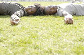 African american couple laying down on green grass in the city. — Stock Photo