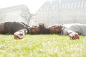 Attractive black couple laying down on green grass head to head, while visiting London city on vacations. — Stock Photo